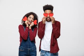 Piękna Afro Amerykańska para trzyma dwa czerwieni papierowego serce, patrzejący kamerę i ono uśmiecha się