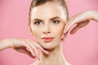 Piękna koncepcja - piękna kobieta rasy kaukaskiej z czystą skórą, naturalne makijaż wyizolowanych na jasnym tle różowy z miejsca na kopię.