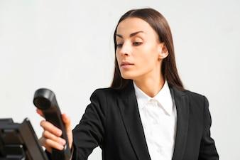 Piękna młoda kobieta trzyma telefonicznego odbiorcę przeciw białemu tłu