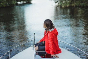 Piękna młoda kobieta w czerwonym płaszczu jeździ prywatnym jachtem. Sztokholm, Szwecja