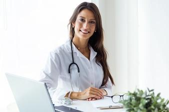 Piękna młoda kobiety lekarka patrzeje kamerę w biurze.