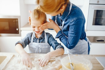 Piękna matka w niebieskiej koszuli i fartuchu przygotowuje obiad w domu w kuchni