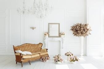 Piękne klasyczne białe wnętrze z kominkiem, brązową kanapą i zabytkowym żyrandolem.