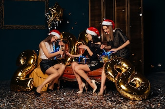 Piękne szczęśliwe kobiety w Santa kapeluszowych otwiera Bożenarodzeniowych prezentach. Bożenarodzeniowy pojęcie