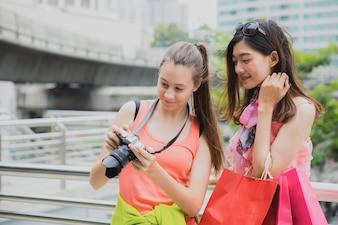 Piękni kobieta turystów przyglądająca fotografia w jej kamerze po podróży