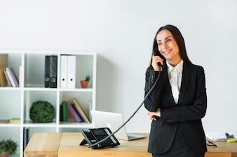 Piękny młody bizneswoman opowiada na telefonicznej pozyci blisko drewnianego biurka