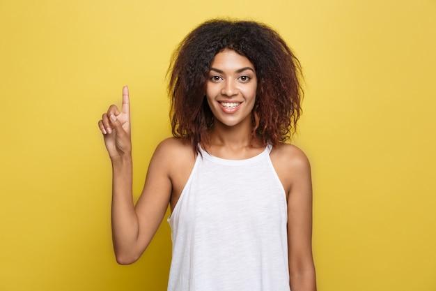 Pi? kna atrakcyjna kobieta ameryka? skiego ameryka? skiego delegowania gry z jej kręcone afro włosy. żółte tło studyjne. skopiuj miejsce.
