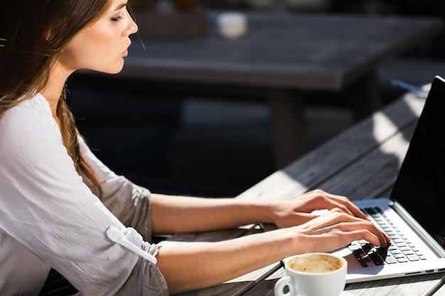 Pi? kna brunetka pracy z laptopem na zewn? trz