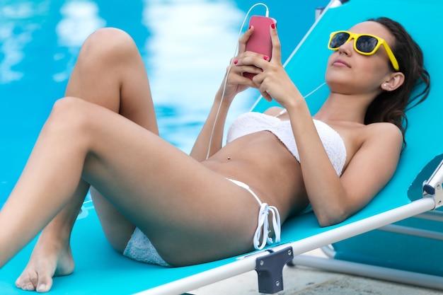 Pi? kna dziewczyna s? uchania muzyki w basenie.