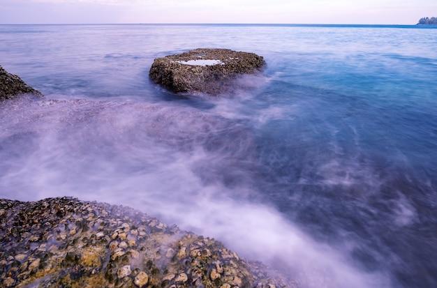 Pi?kny wschód lub zachód s?o?ca scenerii seascape nad tropikalnym morzem w phuket tajlandia epic ?wit krajobraz morski ze ska?ami na pierwszym planie obraz d?ugiej ekspozycji amazing light of nature background.