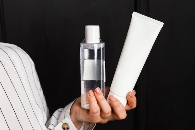 Pianka czyszcząca i toner na kobiecej dłoni. koncepcja kompleksowej pielęgnacji skóry