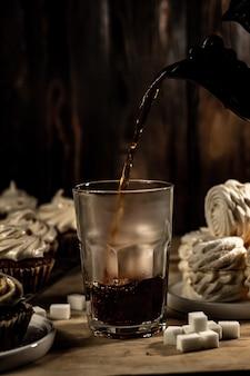Pianka herbaciana i ciastko na tle stołu deserowego