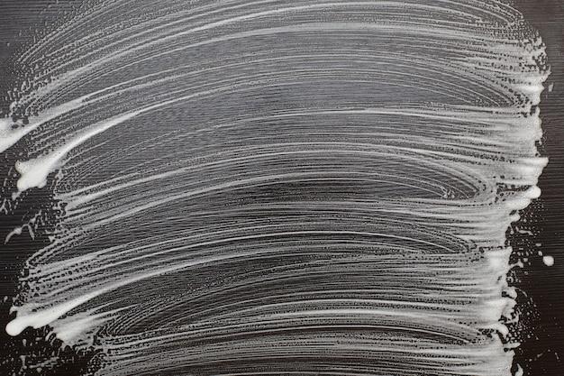 Pianka mydlana na czarnym stole. ślady piany na czarnej powierzchni. skopiuj miejsce.