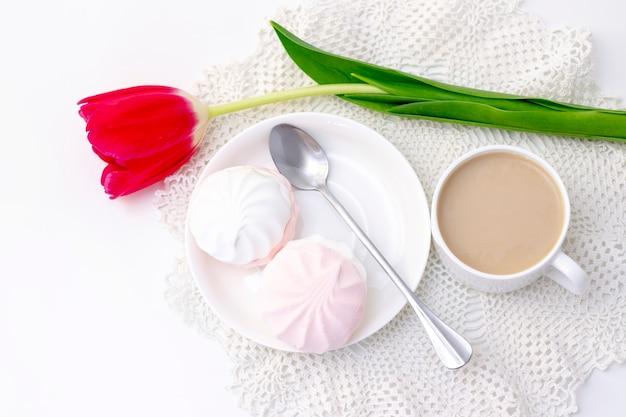 Pianki, herbata lub kawa z mlekiem i kwiatem tulipana. na jasnej powierzchni romantyczny wiosenny poranek. delikatne śniadanie, śniadanie w łóżku. dla ukochanego. niespodzianka.