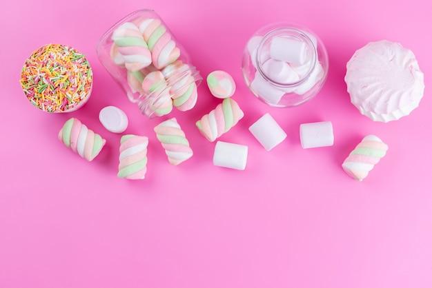 Pianki i bezy z widokiem z góry słodkie i pyszne na różowym, ciasteczkowym słodkim cukrze