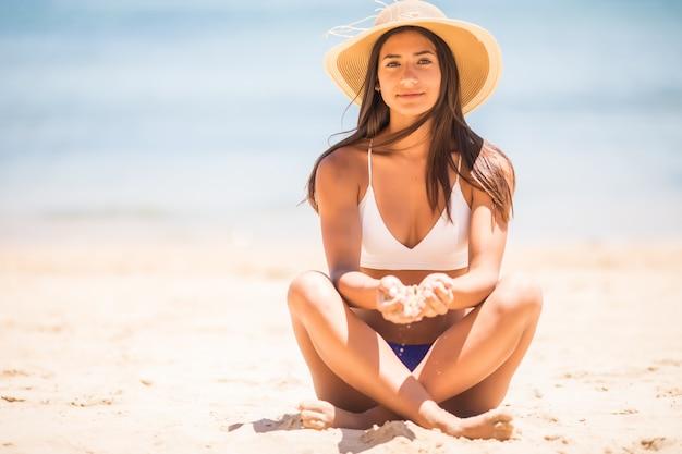 Piasek, gdy czas przemyka ci przez palce. dziewczyna trzyma piasek morze w tle. koncepcja wakacji w cieplejszym klimacie, wycieczka nad morze