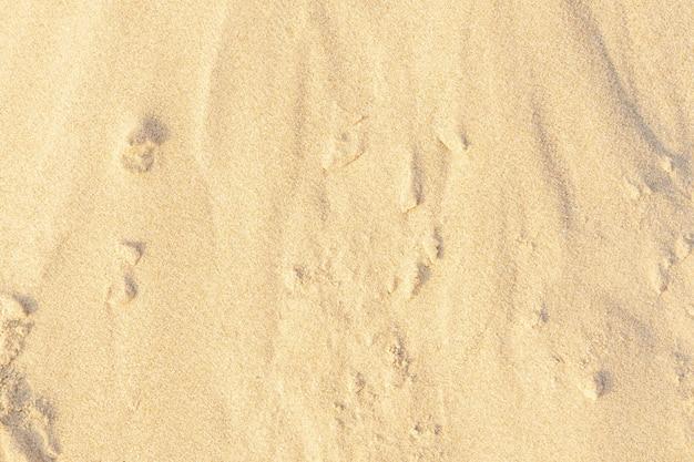 Piasek na plaży jako tło. jasnobeżowy wzór tekstury piasku morskiego, piaszczysta plaża tekstura tło.
