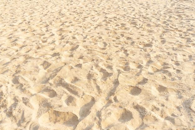 Piasek na plaży w tle. brązowy piasek na plaży tekstury jako tło. zbliżenie.