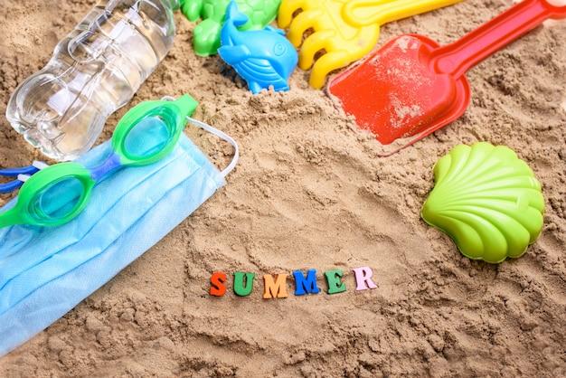 Piasek na plaży z zabawkami dla dziecka, woda, słowo lato kolorowymi literami.