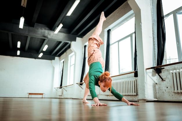Piasek na rękach. profesjonalny trener jogi z koką do włosów wyglądający na skoncentrowanego podczas stawiania na rękach