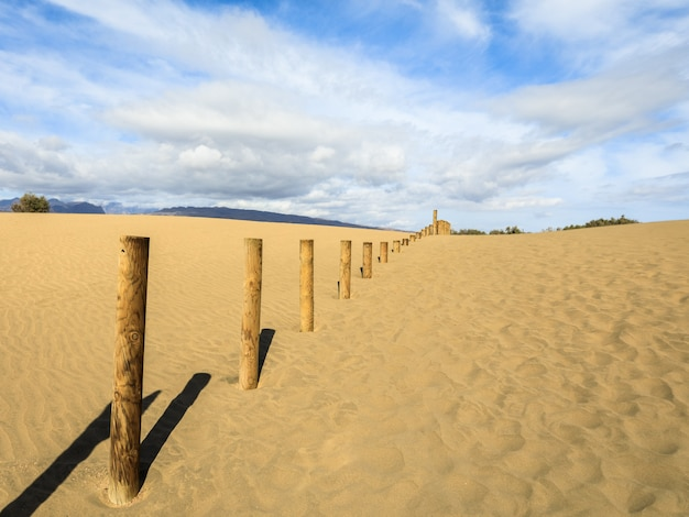 Piasek na wydmach maspalomas, małej pustyni na gran canarii. piasek i niebo oraz drewniany płot oznaczający zakazany obszar rezerwatu ptasiej przyrody la charca.