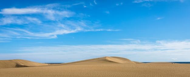Piasek na wydmach maspalomas, małej pustyni na gran canarii w hiszpanii. piasek i niebo. zdjęcie panoramiczne