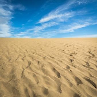 Piasek na wydmach maspalomas, małej pustyni na gran canarii w hiszpanii. piasek i niebo.