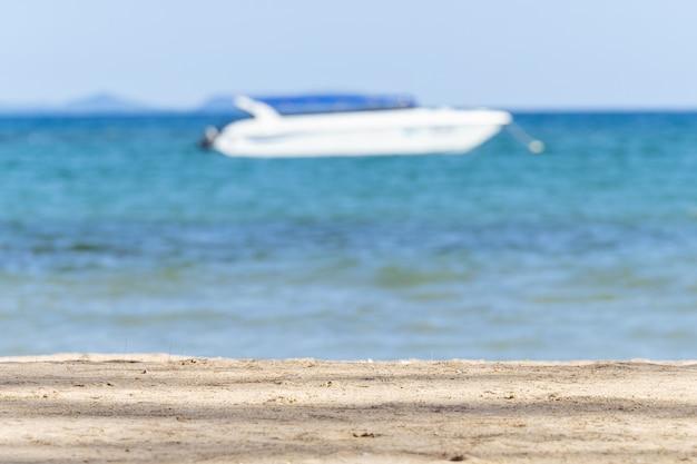 Piasek plaża i blur jasny niebo z łodzią motorową unosi się nad morzem przy koh mak w trat, tajlandia.