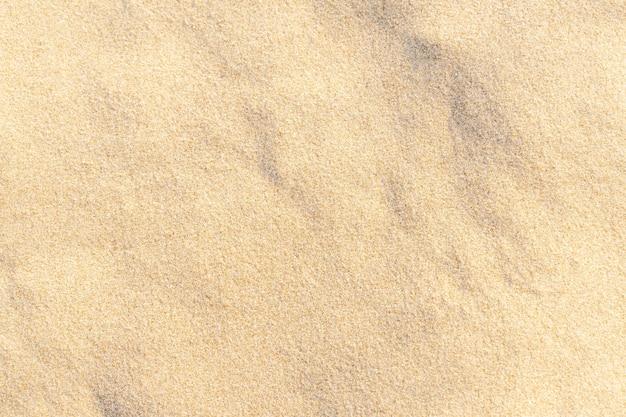Piasek tekstura tło na plaży. jasnobeżowy wzór tekstury piasku morskiego, tło piaszczystej plaży.
