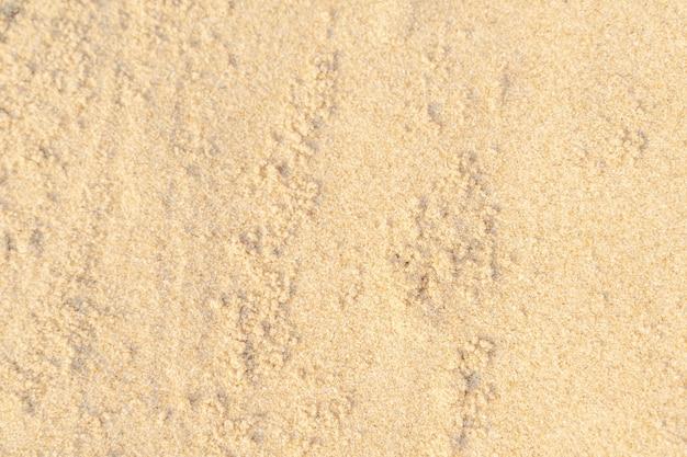 Piasek tekstura tło na plaży. jasnobeżowy wzór tekstury piasku morze, tło piaszczystej plaży.