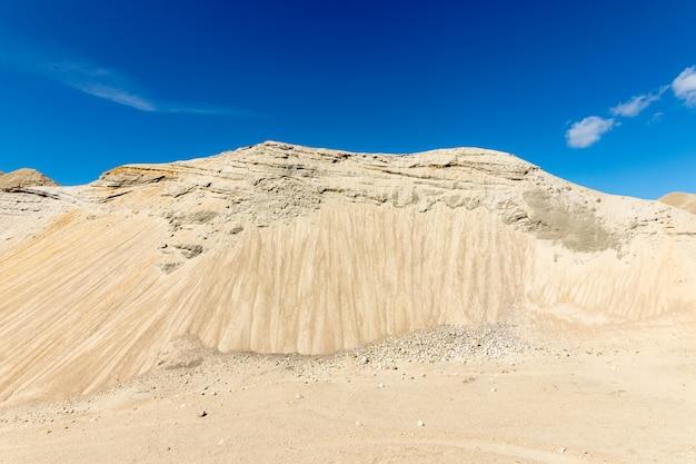 Piasek w dużej piaskowni, błękitne niebo i białe chmury, wzgórze wygląda jak góra