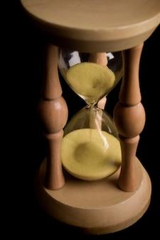 Piasek zegar pokazujący, jak mija czas na czarnym tle