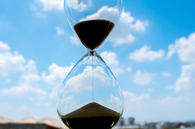 Piaska zegar z nieba i chmury biznesu pojęciem