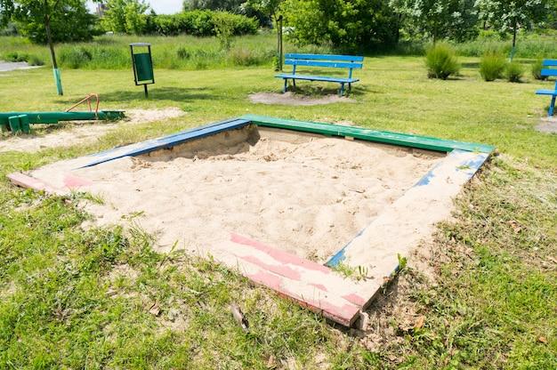 Piaskownica z białym piaskiem na trawiastym placu zabaw