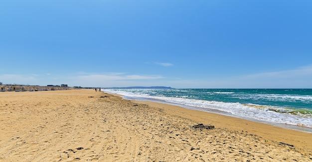 Piaszczysta dzika plaża, błękitne morze z chmurami i błękitne niebo rozmazuje się i filtruje na wybrzeżu. piękny niebieski ocean przyrody na świeżym powietrzu,
