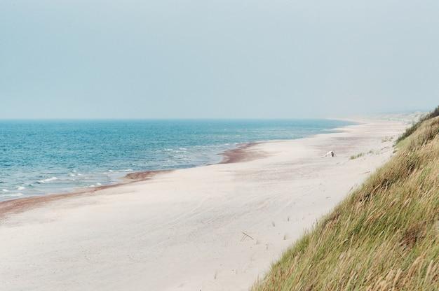 Piaszczysta plaża i błękitne morze. morze bałtyckie, nida, litwa.