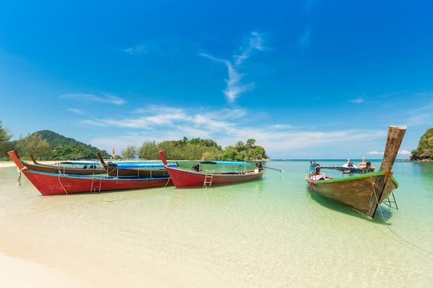 Piaszczysta plaża i łódź z długim ogonem na wyspie kham-tok (koh-kam-tok), piękne morze prowincja ranong, tajlandia.