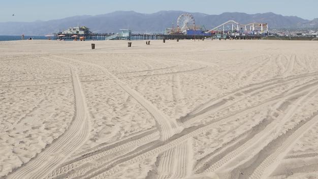 Piaszczysta plaża w kalifornii, diabelski młyn na molo w kurorcie santa monica na pacyfiku. los angeles, usa.