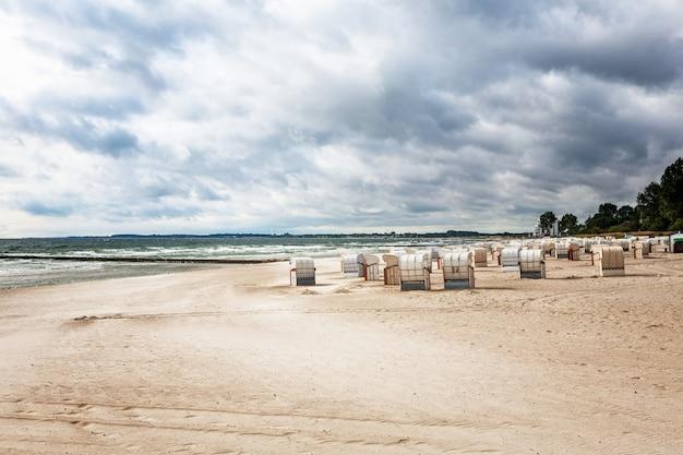Piaszczysta plaża z leżakami. późne lato krajobraz z zachmurzonym niebem. tło wakacje. wybrzeże bałtyku, cel podróży