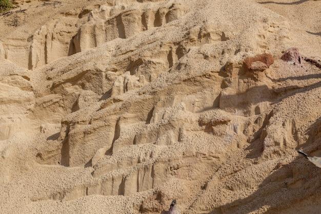 Piaszczysta plaża z wzorami ze strumieni wody faktura piaszczystej powierzchni a