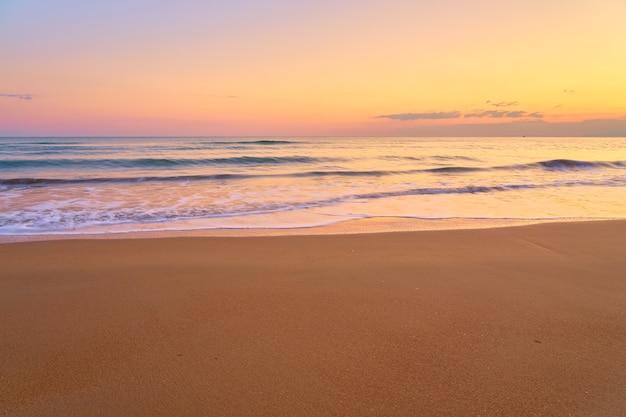 Piaszczysta tropikalna plaża o zachodzie słońca
