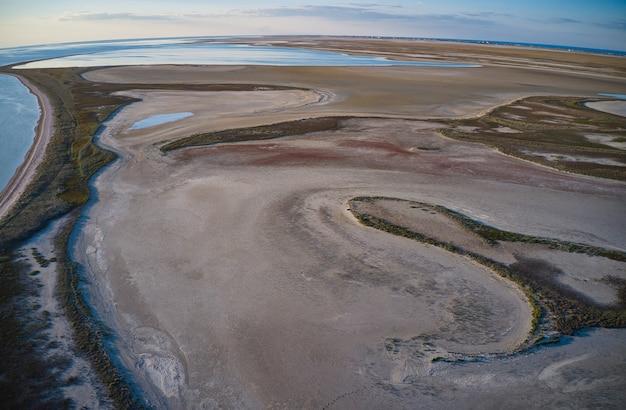 Piaszczyste bagno w pobliżu pięknego jeziora, kamera z drona