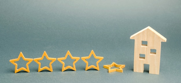 Piąta gwiazda jesieni w pobliżu miniaturowego drewnianego domu. koncepcja upadku ratingu hotelu lub restauracji