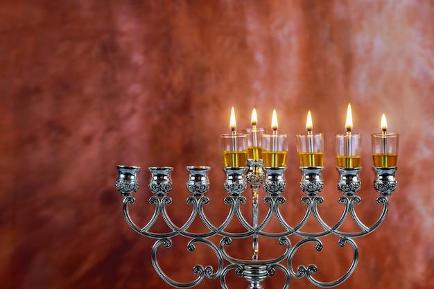 Piątego dnia żydowskiego święta chanuka pali sześć świec chanuka na świetle