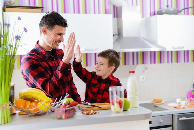 Piątka. szczęśliwa ojca i syna odświętności drużyna pracuje przy kuchnią. siedząc przy stole pełnym świeżych owoców i przygotowując śniadanie.