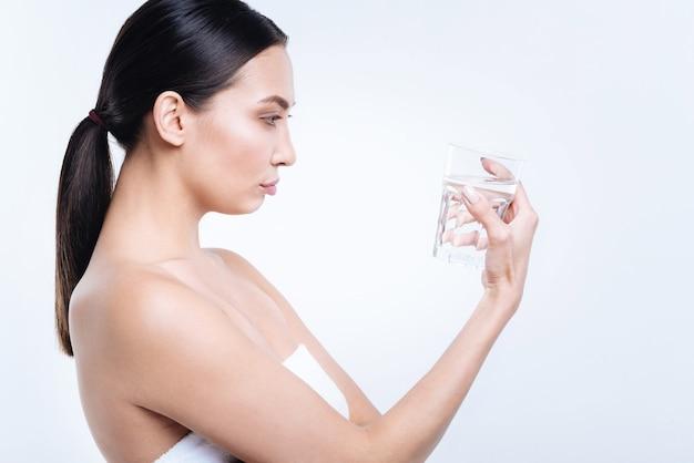 Pić czy nie. widok z boku ślicznej ciemnowłosej kobiety patrzącej na szklankę wody w dłoniach, stojącej owiniętą ręcznikiem, pozującej przy białej ścianie