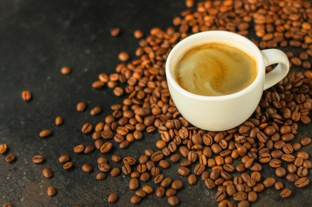 Pić kawę w białej filiżance i posypać ziarna kawy na stole