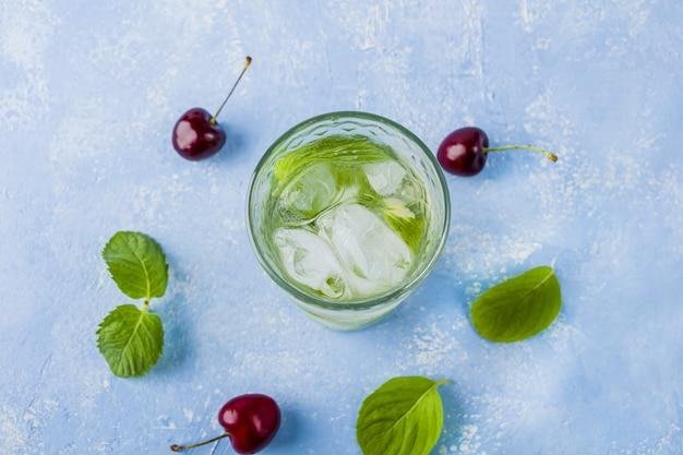 Pić z limonką, wiśnią i miętą. letnie lemoniady lub mrożona herbata. koktajle mojito z kostkami lodu.