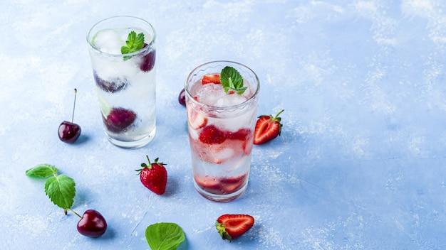 Pić z truskawką, limonką, wiśnią i miętą. letnie lemoniady lub mrożona herbata. koktajle mojito z kostkami lodu.