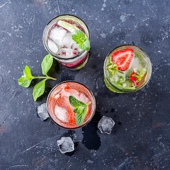 Pić z truskawką limonkowo wiśnią i miętą na ciemnym tle. koktajle mojito